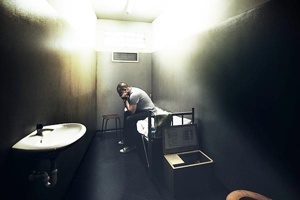 One man sitting on a bed in a small cell of a dark prison.